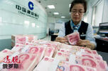 A clerk counts Chinese 100 yuan banknotes CN