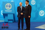 Russian President Vladimir Putin, left, shakes hands with Chinese President Xi Jinping CN