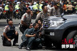 Police officers react near the site of a blast in Jakarta CN