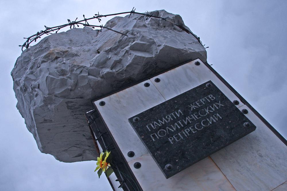Il monumento alle vittime dei gulag è un masso abbozzato con filo spinato arrugginito. Intorno le case di Rudnik, sopra la riva del fiume Usa
