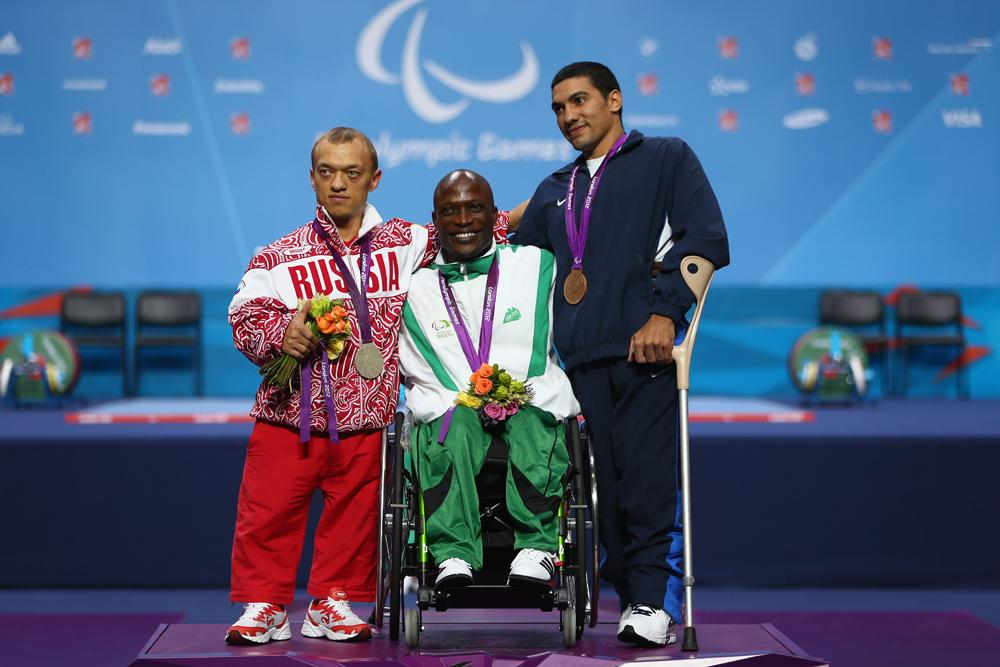 Gold medalist Yakubu Adesokan (C) of Nigeria alongside silver medalist Vladimir Balynetc (L) of Russia and bronze medalist Taha Abdelmagid (R) of Egypt in the Men's 48kg Powerlifting on day 1 of the London 2012 Paralympic Games at ExCel on August 30, 2012 in London, England.