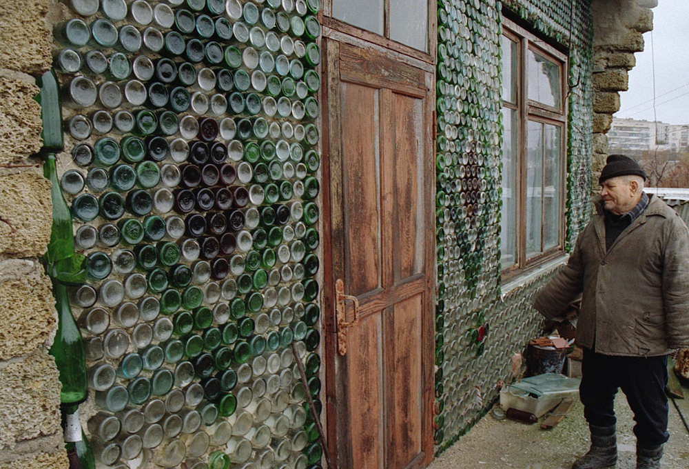 Georgy Vashchenko, 76, standing near the entrance of his dwelling. Its front side is built of empty champagne bottles.