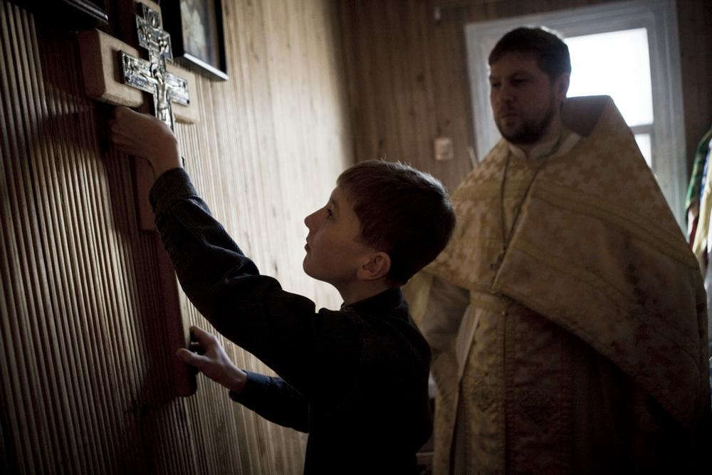 There is a simple greatness of daily life which can only be revealed far from big cities. Meet Valery Klamm friends, the Siberians. // Fyodor helps to his father - Orthodox priest Roman - during the Sunday Service. Uspenskiy Cathedral, Bagan Village, Novosibirsk Region, 2011