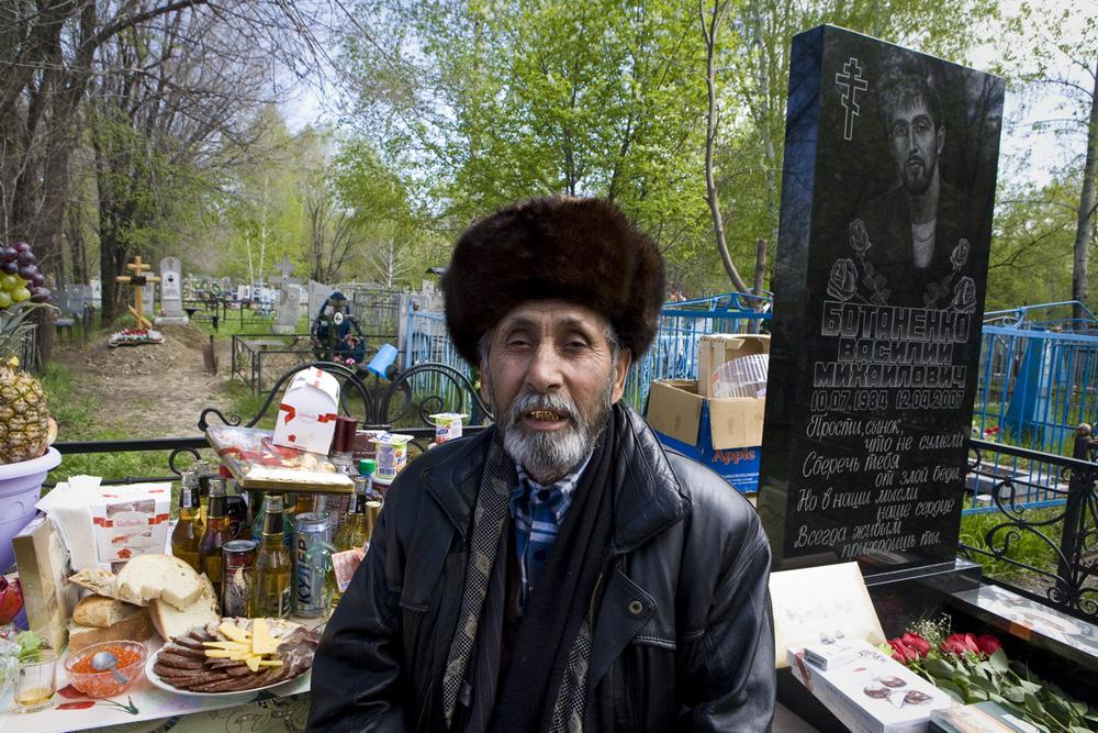 "Holy Trinity Day. People remember those who died and share food and drinks with them. Gipsy ""Uncle"" Misha at the son's grave. Biysk, Altay region, 2010"