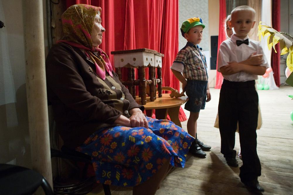 A women calms down her grandchildren before a public performance in the local House of Culture. Barabinsk, Novosibirsk region, 2009