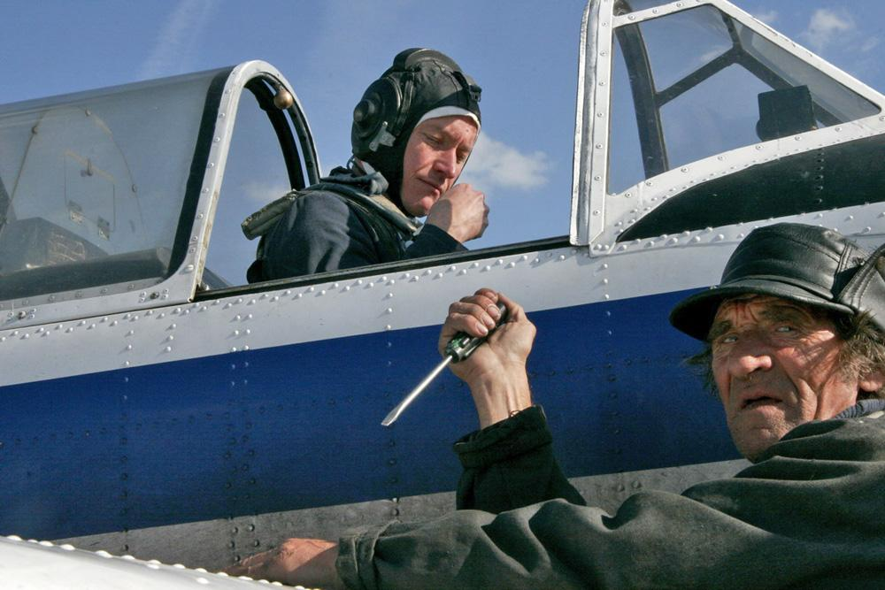 "Part-time aircraft mechanic and a full-time pensioner ""Uncle"" Gena prepares the machine and the man for flight. Training aerodrome ROSTO, Kislovka Village, Tomsk region, 2006"