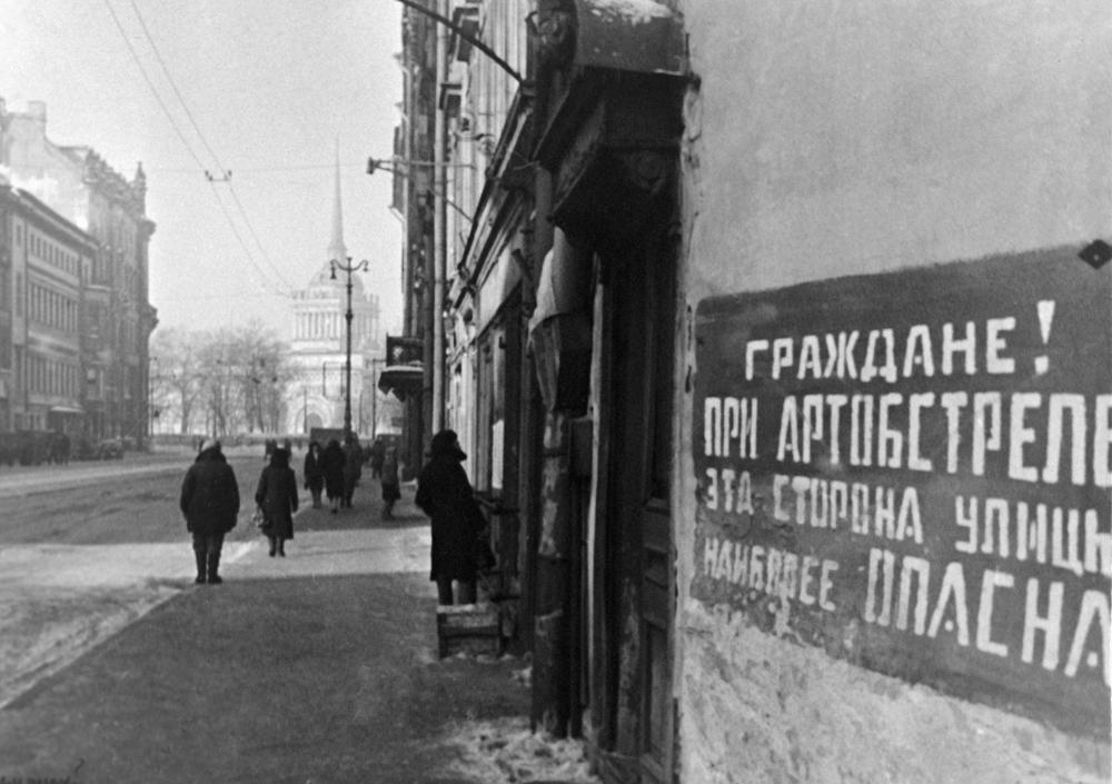 "The siege of Leningrad started in early autumn 1941. // The sign on the house reads, ""This side of the street is most dangerous during bombings""."
