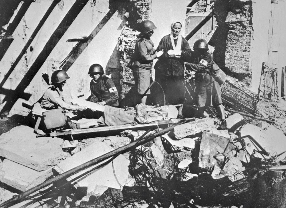The only way for supplies to reach the city was the Road of Life, ice transport route across the frozen surface of Lake Ladoga. // Nurses helping an old woman in a ruined house. The siege of Leningrad.
