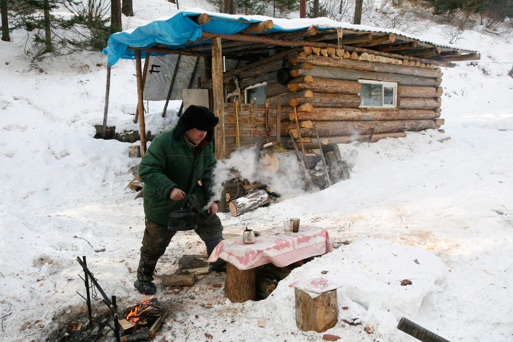 Yushkov makes tea after driving to his self-built hunting lodge river in a remote taiga area.