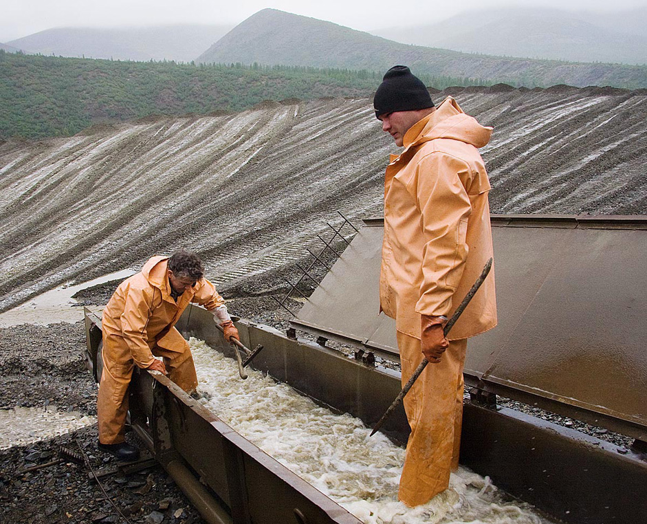 Workers open the lid of the trough and set about collecting the gold. Flushing the mats. Large chunks of ore are removed first.
