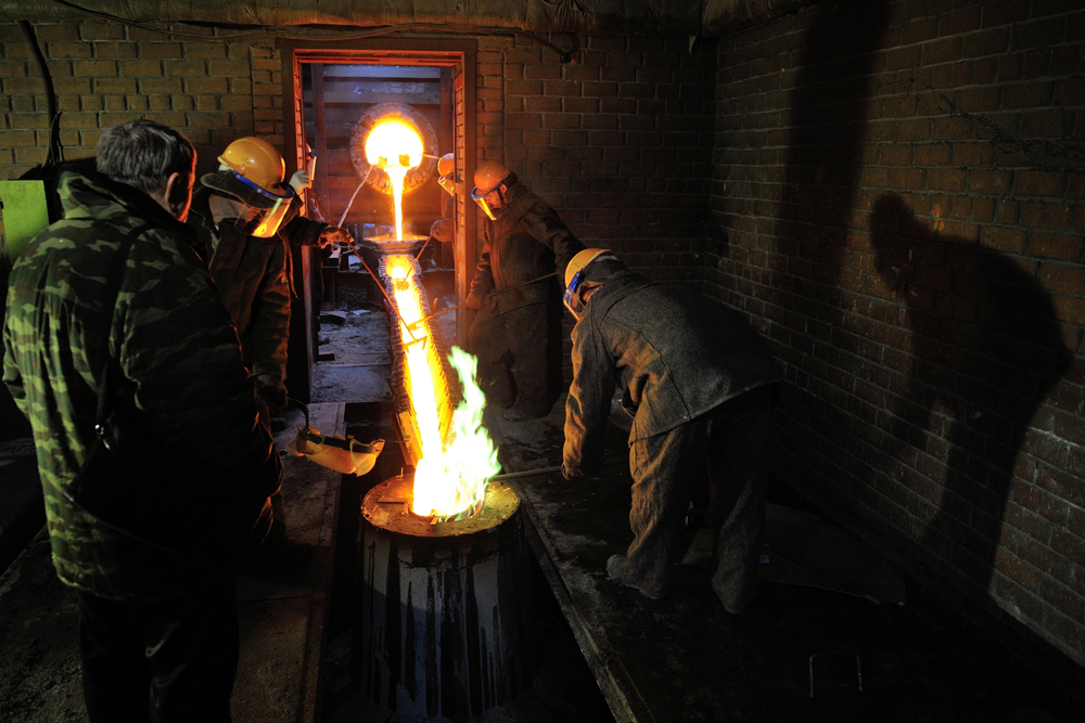 The liquid metal first trickles and then flows as a stream of fire into the black opening in the cast.