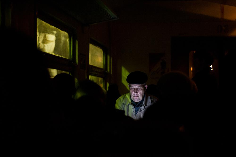 A man peers at the display in a train car with the lights off.