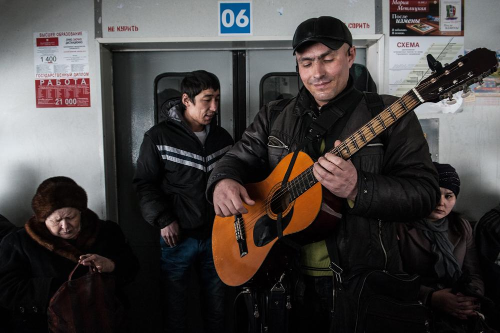 A musician plays on board a train. During a 30-minute train ride, you can expect to see more than a dozen different sellers, buskers, spoken-word poets, singers, and beggars.