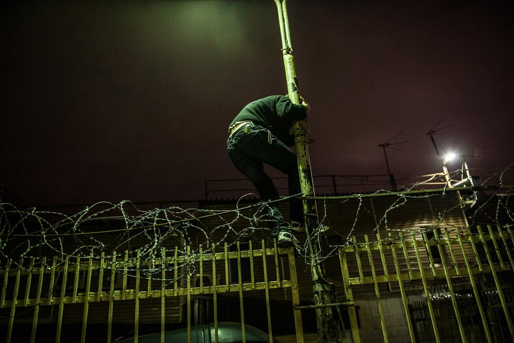 A farebeater sneaks through the barrier at a rail station. Some suburban rail stations have been turned into outposts with spiked fences wrapped in barbwire and smeared with something that leaves a stain. But even that does not deter some passengers, so the fences are sometimes guarded by Russian Railways security staff, who are always ready to drive off would-be deadheads.
