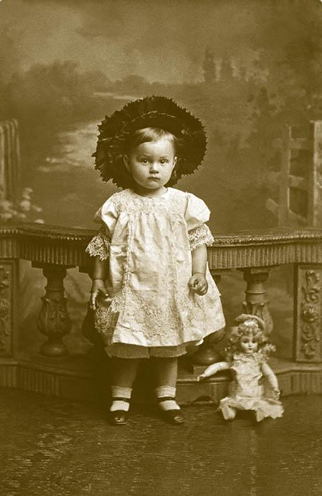 """A new approach to girls' dresses came from the U.S. — pleated skirts with a small yoke on top. The style afforded the child full freedom of movement, and due to its practicality remained in use for a hundred years. A new element in girls' fashion was the elegant """"cabriolet"""" hat-hood in the style of the 1830s, made of homespun felt and trimmed with black ostrich feathers and taffeta ribbons."""