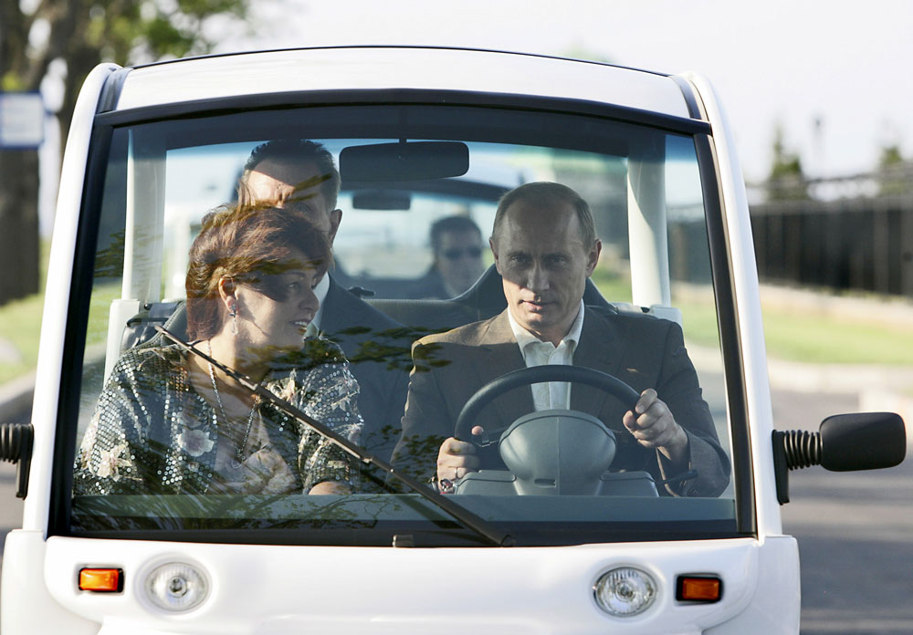 President Vladimir Putin and his wife Lyudmila seen in an electric motor car prior to dinner with U.S. President George W. Bush and first lady Laura Bush at the G8 summit site in St.Petersburg, Russia, Friday, July 14, 2006.