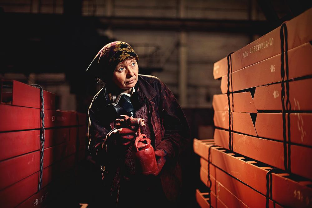 In the photo: this woman with a sprayer paints metal structures. Sibenergomash Plant in Barnaul.