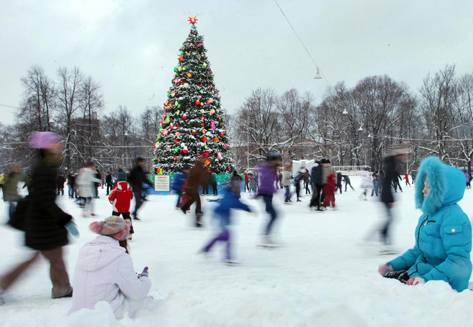 People ice skating on an open-air skating rink in Saint Petersburg's at Kirov Park with a Christmas tree in the background.