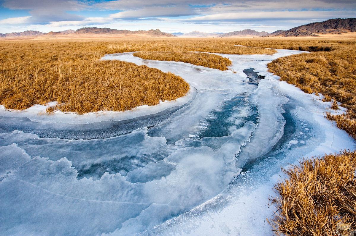 The frozen Kan River slices through the steppe in icy veins. Ust-Kan, Altai