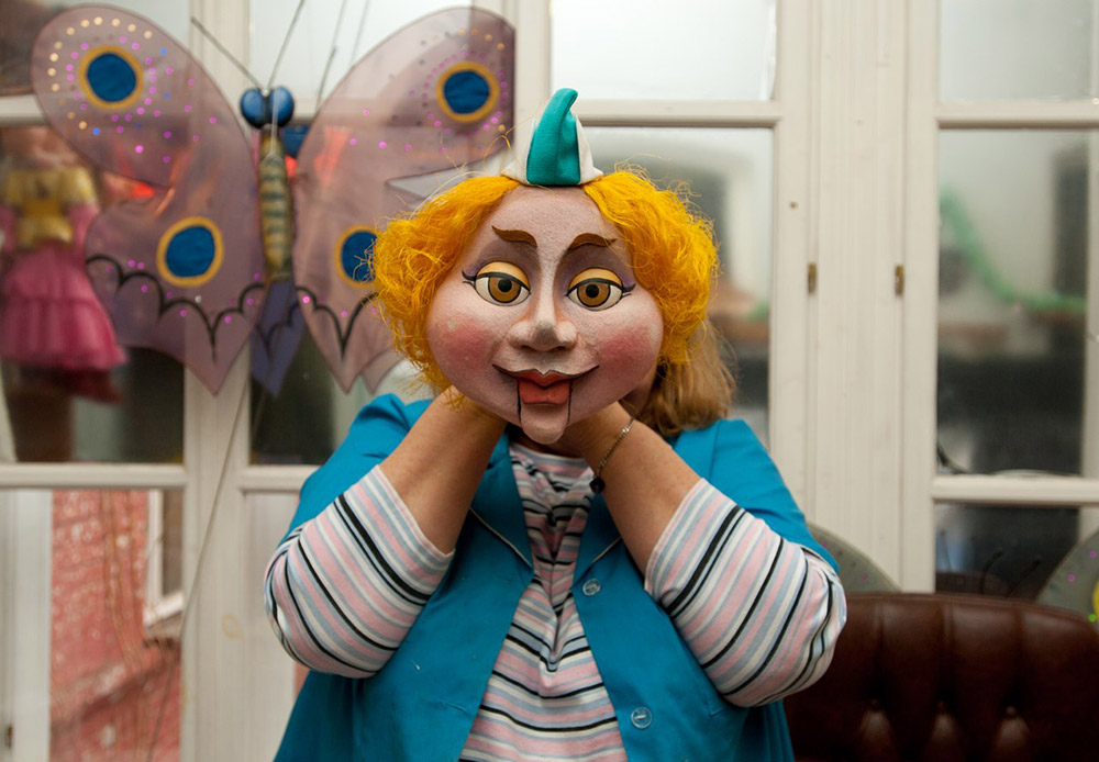 The theater's head puppeteer, Olga Belogorskaya, with a mask.