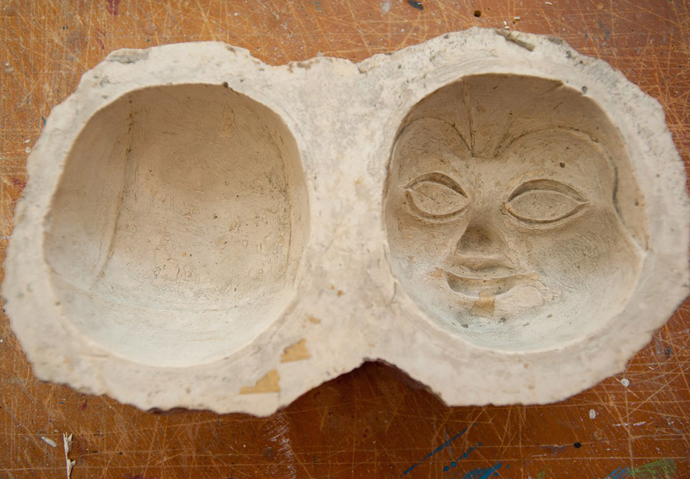 One of the most difficult tasks in creating a puppet is making its head. The process begins by creating a clay sculpture whose shape will be used to subsequently pour two plaster forms. When these two halves are ready, they are papier-mached. After they dry, the parts of the future puppet's head are glued together and trimmed.