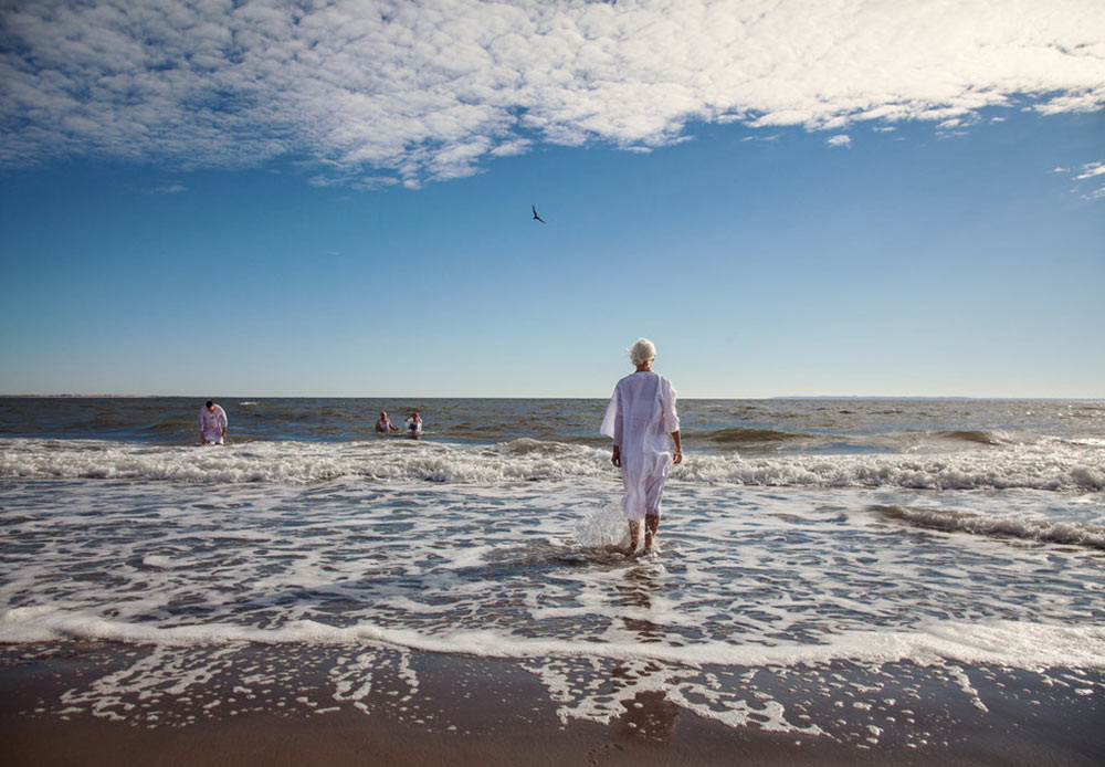 Women walking into the sea during an Epiphany ceremony in Brighton Beach, New York. January 19, 2013.