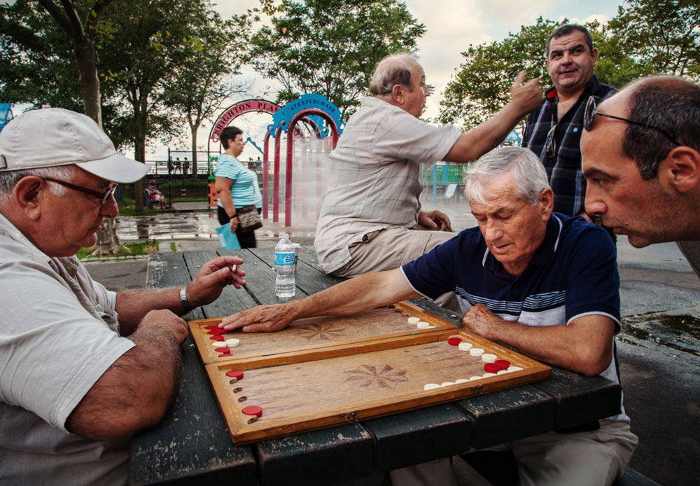 """Ukrainian photographer Yulia Bazar captured Brighton Beach's streets and named the series """"Little Odessa"""". // Playing cards, often for money, has become a usual routine among male immigrants. Brighton Beach, New York. July 30, 2012."""