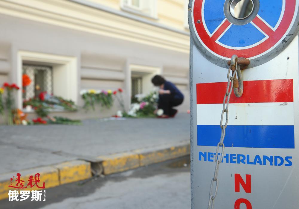 于荷兰大使馆处,一位莫斯科女士献上一束花。