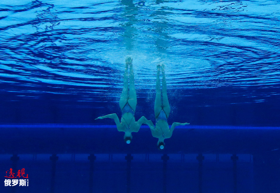 图中:俄罗斯花样游泳双人项目选手斯维特兰娜•罗马什娜与娜塔莉亚•伊先科正在2012年伦敦奥运会上进行规定动作表演。