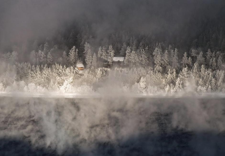 """Bathhouse."" Taken in heavy frost on the Yenisei, from an observation point in the region of Ovsyanka. Usually in such cold the river gives off so much steam that it blankets the opposite shore. Here a gust of wind carved a fleeting window in the mist, only to be enveloped once more in white silence."