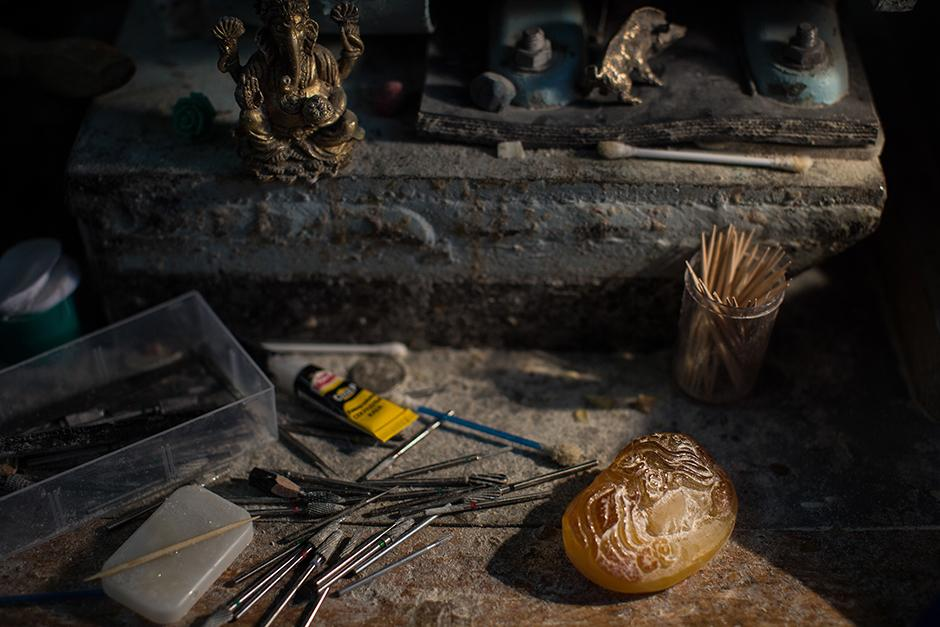 """Amber craftsman Yury Sorokin grinds a piece of amber at the Amber Combine's workshop. """"You can start working on one design, but then see that the amber leads you,"""" he says."""