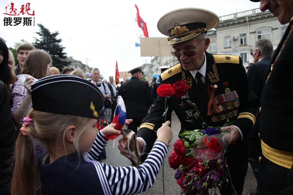 纪念伟大卫国战争胜利69周年以及塞瓦斯托波尔解放70周年的胜利者大阅兵。孩子们向伟大卫国战争老战士献花。拍摄日期:2014年5月9日。
