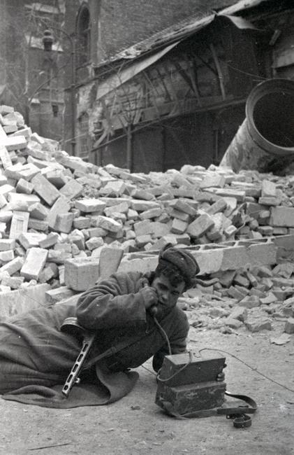 战地通讯兵普罗宁(Pronin)在布达佩斯巷战期间通过电话传达情报。匈牙利,布达佩斯,1945年2月。