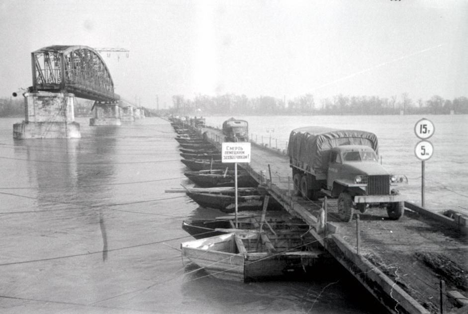 苏联士兵乘坐载重汽车通过多瑙河上的临时浮桥到达布达佩斯另一侧。右侧是被破坏的桥。匈牙利,布达佩斯,1945年2月。