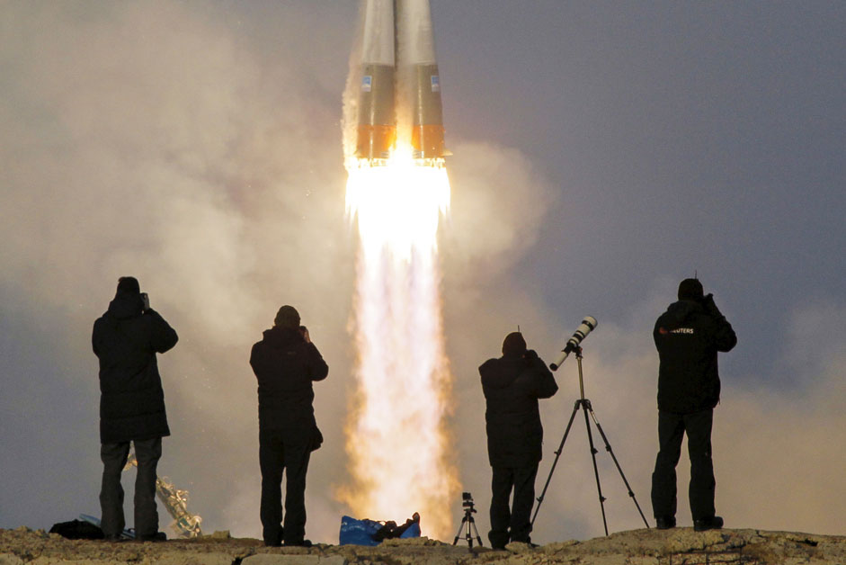 Photographers take pictures as the Soyuz