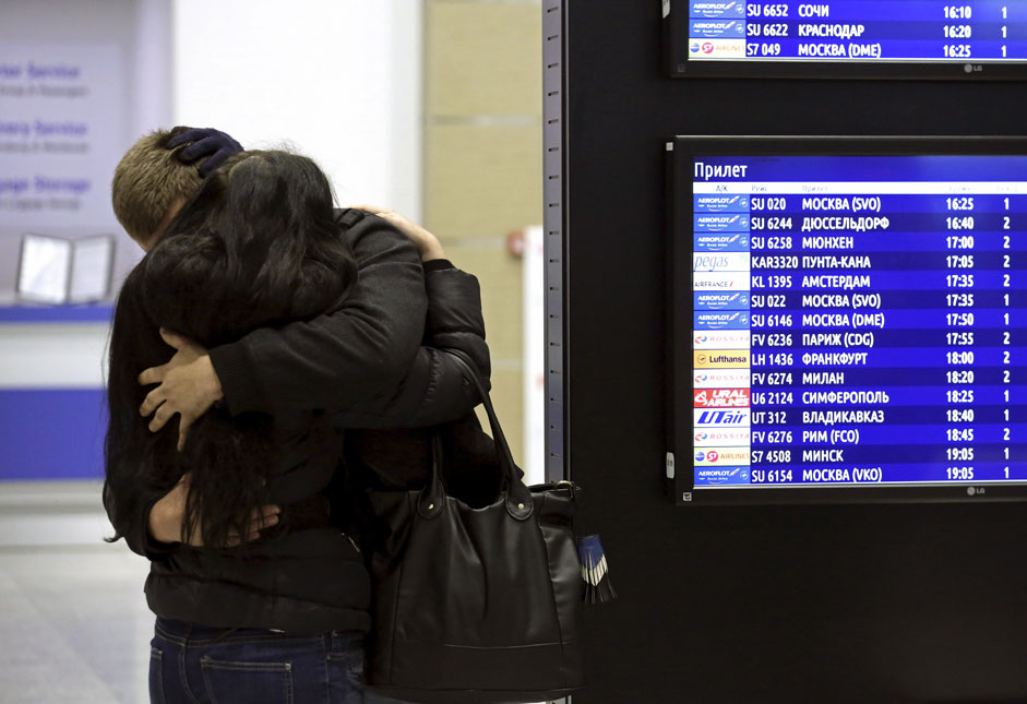 A couple embraces next to a flight information board at Pulkovo airport in St. Petersburg