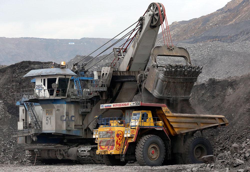 Employees operate a machine and a BelAZ dump-body truck