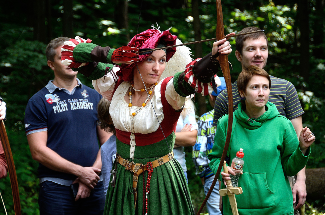 woman dressed as an archer performs during