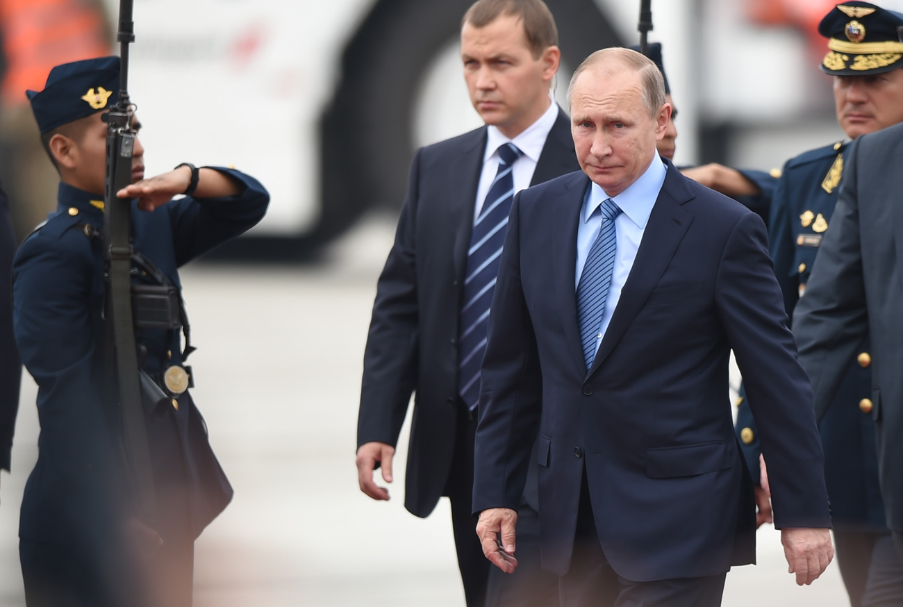 Russia's President Vladimir Putin walks upon arrival at Jorge Chavez International Airport in Lima