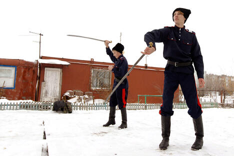 Russian Cossacks Vitaly Timoshenko (R), 19, and Vyacheslav Timoshenko, 13, juggle swords in the town of Krasny Oktyabr, on the outskirts of the southern Russian city of Volgograd, January 5, 2014. According to local media, over 400 Cossacks arrived at Sochi on January 9 to provide security for athletes, foreign delegations and tourists, following the two recent suicide bomb attacks in Volgograd.