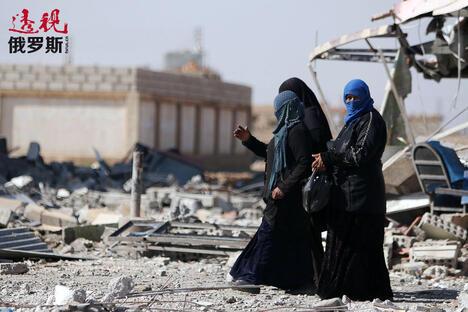 Women walk on rubble in al-Shadadi town CN