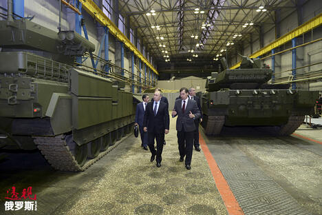 Russian President Vladimir Putin (L) listens to Andrei Terlikov, the head of the Ural Transport Machine Building Design Bureau CN