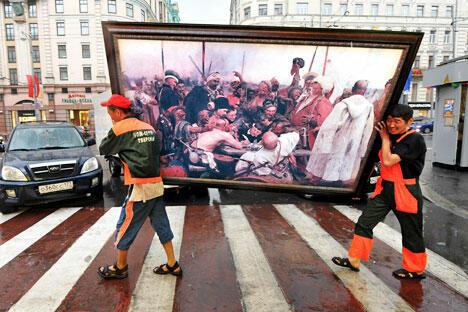 两名劳工移民抬着俄罗斯著名画家列宾作品的复制品经过莫斯科市中心。摄影: AFP / East News