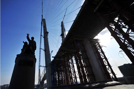弗拉迪沃斯托克市内的一座铜像,纪念在第二次世界大战中丧生的贸易船队的海员,一旁是正在建设的通往俄罗斯岛的大桥。摄影:俄新社