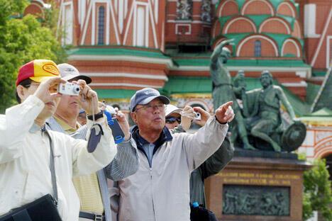 图中:游客身后是圣瓦西里大教堂以及英雄米宁和波扎尔斯基雕像。图片来源:塔斯社