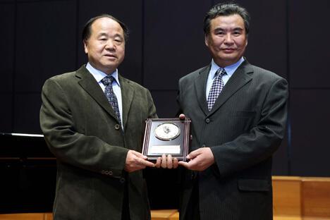 10月11日,中国作家莫言获得2012年诺贝尔文学奖。图中:这是在第八届茅盾文学奖颁奖典礼上,中国作家协会党组书记李冰为获奖作家莫言(左)颁奖(2011年9月19日摄)。 图片来源:新华社