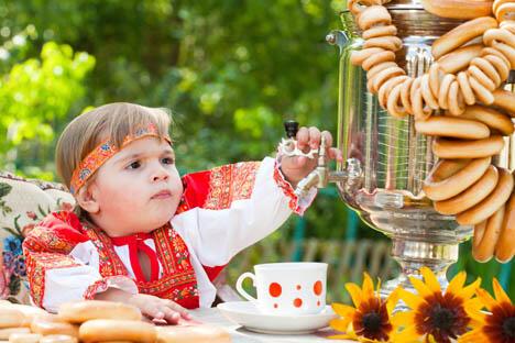 一个身穿民族传统连衣裙的小女孩正在从挂满了面包圈的茶炊中倒茶喝。图片来源:lori/Legion Media
