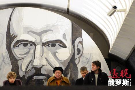 """莫斯科地铁站一直被公认为世界上最漂亮的地铁站,享有""""地下的艺术殿堂""""之美称。图中:乘客身后的墙壁上正是俄罗斯著名作家陀思妥耶夫斯基。 图片来源:AFP"""