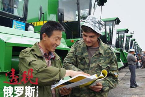 乌苏里斯克。来自中国哈尔滨的农业工人和滨海边疆区的农业机械师正在学习来自中国的机械设备的技术手册。图片来源:塔斯社