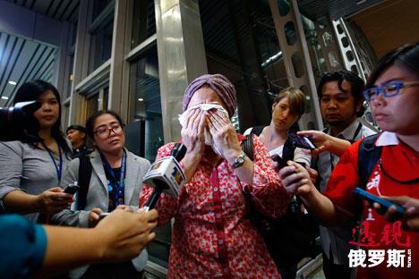 电视记者试图采访一个正在哭泣的女人,她正焦急等待马航坠落后的更多信息。图片来源: Reuters
